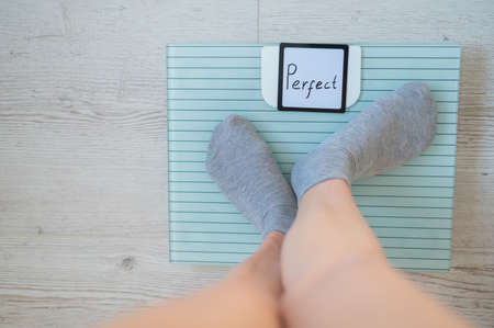 Faceless woman measures weight on the floor scales. Top view of womens feet in gray socks on the scales with the word perfect. The inscription on the screen is perfect. There is no excess fat.