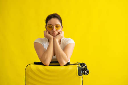 Unhappy woman in sunglasses hugs a suitcase on a yellow background. An upset girl missed her flight on a plane. Cancellation of all flights due to coronavirus. Lack of summer vacation. Imagens
