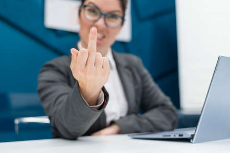 Angry business woman in a suit shows a middle finger while sitting at a desk. Annoyed female office worker showing a fuck you gesture. Professional burnout. Stok Fotoğraf