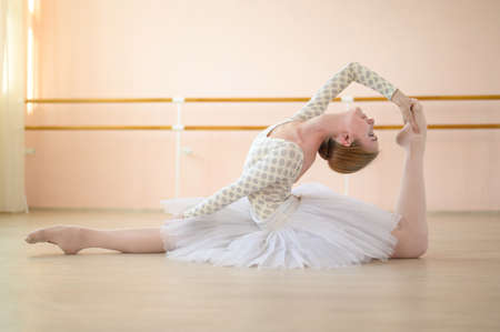 Beautiful ballerina in body and white tutu is training in a dance class. Young flexible dancer posing in pointe shoes sitting on the floor. Banque d'images - 151044792