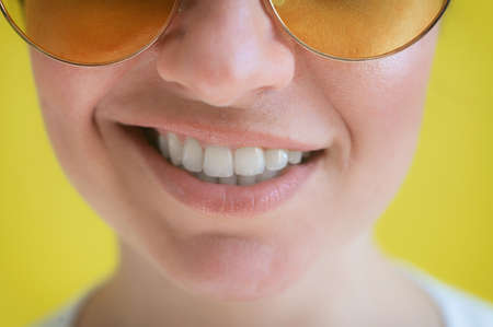 Close-up of a female smile on a yellow background. Cropped photo. Woman with a perfect smile in sunglasses.