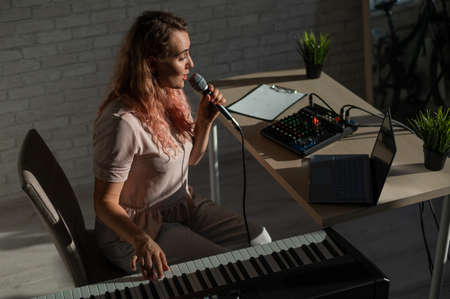 A female blogger sings and plays the live electronic piano. Portrait of a girl recording a song on a web camera and composing on a synthesizer. Online music lessons. Distance learning in quarantine.