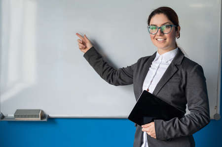 Beautiful red-haired woman in a suit with a digital tablet in her hands. A smiling female teacher with glasses stands in a school class and points a finger at a white board. Educational institution.