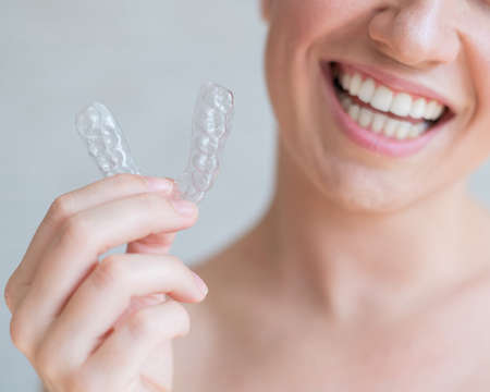 Close-up of orthodontic silicone transparent teeth aligner in female hands. A woman with a perfect charm smile holds a removable night retainer. Bracket for teeth whitening. Cropped photo. 免版税图像