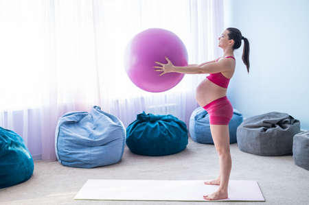 A pregnant woman in sportswear is doing gymnastics for pregnant women. The girl is engaged in fitness with a ball for expectant mothers. Last trimester. 免版税图像