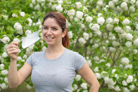 Happy red-haired woman takes off a medical mask while standing next to a blossoming apple tree in a park. Ending seasonal allergic rhinitis. The girl was cured of an allergy to pollen.