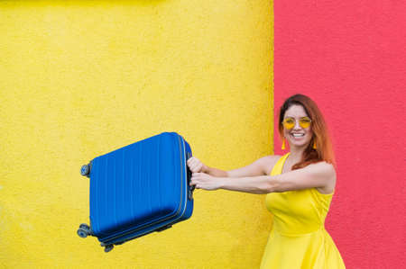 Happy woman in a whip on a yellow-red background joyfully waves a suitcase in anticipation of travel. Beautiful girl in sunglasses with a blue bag in her hands. Baggage for summer vacation.