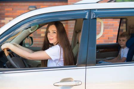 SUVを運転するヨーロッパの女性。幸せなお母さんと息子が車の中に座っています。チャイルドシートの男の子。家族は車で旅行を楽しんでいます。 写真素材