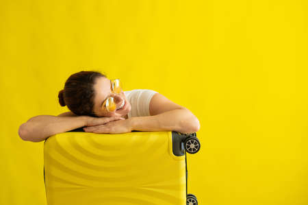 Smiling girl in sunglasses laid her head on a suitcase on a yellow background. Happy woman with hand bag awaiting trip. Luggage on wheels. Imagens