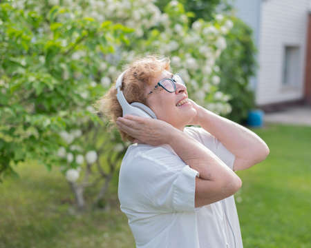 An elderly Caucasian woman walks in a park and listens to music. A smiling grandmother enjoys the aroma of flowering trees in the garden on a warm sunny day.