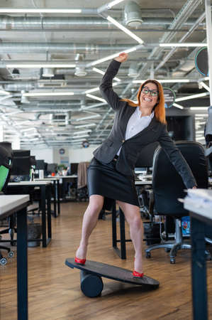Cheerful business woman in red high heel shoes lost equilibrium on the balance board and falls. A female employee in a suit does sports at the workplace during the break. Bad coordination. 免版税图像