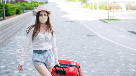 A beautiful young Caucasian woman in a medical mask walks down the street with a red suitcase. A girl with luggage travels alone during the height of the coronavirus epidemic. The empty city.