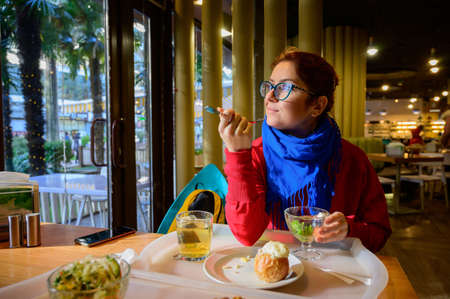 Red-haired caucasian woman eating salad in a cafe. Pensive romantic girl in glasses and a blue scarf is having lunch.