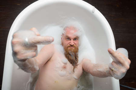 Cheerful bearded man takes a bath with foam and shows middle fingers. Top view of a bald aggressive man gesturing go fuck you.