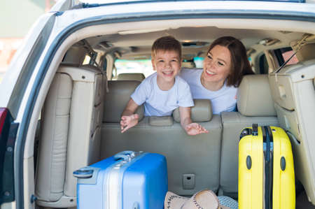 Happy European woman with her little son look back at the trunk of a car with suitcases. Family summer vacation. Traveling by car with a child. A boy with his mother in the back seat.