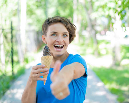 Charming Caucasian woman with a short haircut smiles and eats an ice cream cone and shows a thumb. Emotional girl with a beautiful smile enjoys gelato walking in the park. 版權商用圖片