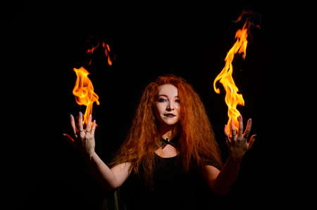 A witch with long curly hair holds a magic fire. Tongues of flame on the palms of a red-haired woman. Фото со стока