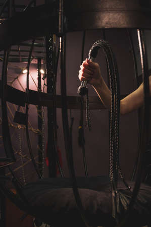 Female hand with a long woven leather lash in a cage. BDSM Punishment and pleasure. Cropped Stock Photo