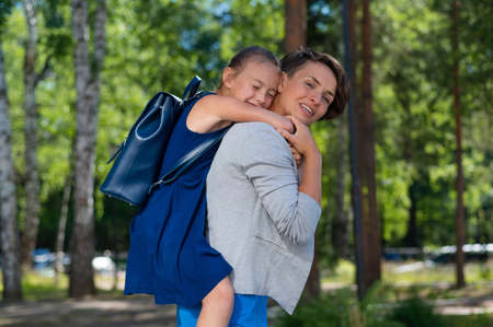 A beautiful caucasian woman stands outdoors and holds daughter on her back. A cheerful smiling girl sits on her mother back while walking in the park. Friendly loving family.