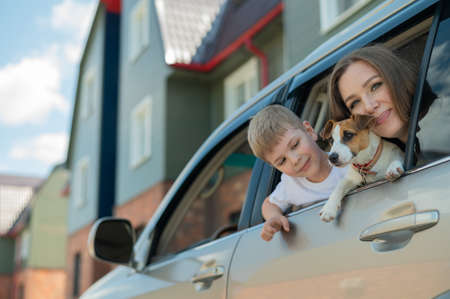 Beautiful caucasian woman travels with a child and a dog. Mom and son leaned out of the car window in an embrace with a puppy of Jack Russell Terrier. Happy family go on a car trip. Zdjęcie Seryjne