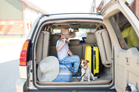 Happy boy in a cowboy hat and puppy jack russell terrier travel by car. A child and a funny little dog are sitting in the trunk and are ready for summer vacation. Independent travel. Best friends.
