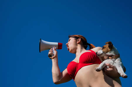 Caucasian woman in red bikini works as a lifeguard on the beach and shouts through a megaphone against a blue sky. Girl holds puppy jack russell terrier and loudspeaker. Summer vacation. Zdjęcie Seryjne