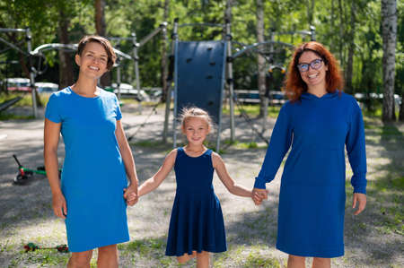 Homosexual lesbian couple hold daughters hands. A girl walks with two mothers in the park. Two married women and a child outdoors.