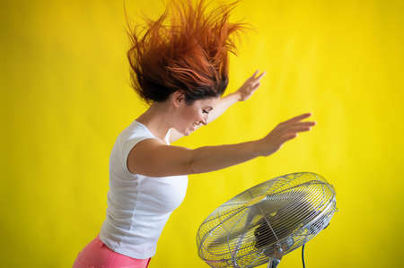 A beautiful red-haired woman is cooled off standing over a large electric fan on a yellow background. Girl with hair developing in the wind. Device for cooling the air.