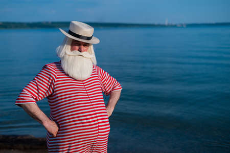 Elderly gray-haired man with a beard in a striped bathing suit and hat posing on the beach. Senior citizen on vacation by the lake. Zdjęcie Seryjne