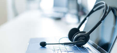 Call center operator desktop. Close-up of a headset on a laptop. Help desk. Workplace of a support service employee. Headphones with a microphone for voip on a computer keyboard. Banque d'images