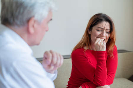 An upset woman bites her nails at a session with a male psychologist. Mature gray-haired psychotherapist talking to a female patient with depression and neurosis. Unbalanced psyche. Onychophagia.