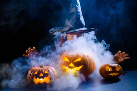 An ominous witch in a hat conjures over a jack-o-lantern. Traditional halloween characters. Mystical fog creeps over pumpkins with carved terrible faces. An evil witch casts a spell. 스톡 콘텐츠