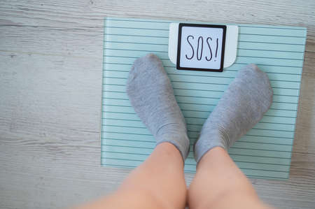 The fat woman is weighed. A top view of female feet in gray socks stands on an electronic scale. SOS inscription on the display of the floor scale.