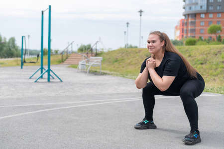 Fat girl is engaged in fitness on the sports field. Beautiful young smiling overweight woman crouches outdoors. Bad eating habits. Exercises on the muscles of the buttocks.