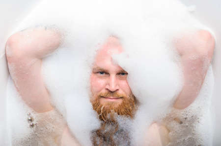 Close-up portrait of funny red-bearded bald man taking a bath with foam. Cheerful naughty guy at spa treatments. A parody of glamorous girls. Foto de archivo