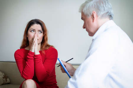 Caucasian woman cries and holds hands on her face at the session of a psychotherapist. A gray-haired male psychologist is talking to a female patient. Treatment of chronic depression and panic attacks Foto de archivo