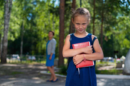 Unhappy girl with a book does not want to go to school. Mother sends daughter to first grade. The first day in elementary school.