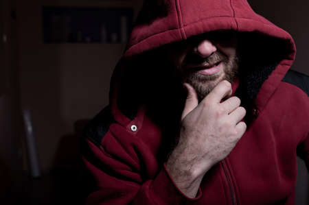 Portrait of an evil bearded man in a hoodie in the dark. Male criminal hides his eyes under the hood.