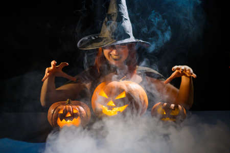 An ominous witch in a hat conjures over a jack-o-lantern. Traditional halloween characters. Mystical fog creeps over pumpkins with carved terrible faces. Woman in carnival costume.