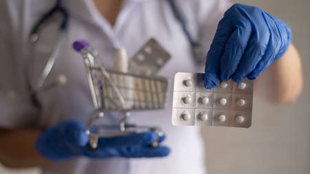 A faceless female doctor in rubber gloves shows a blister with pills and holds a mini shopping cart with a full pack of different medicines. Pharmacist recommendations.