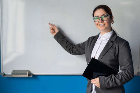 Beautiful woman in a suit with a digital tablet in her hands. A smiling female business coach with glasses stands in a conference room and points a finger at a white board. Workshop at the office.