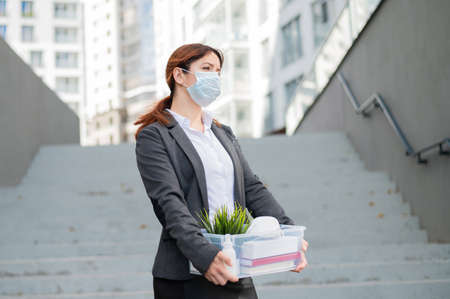 Unhappy woman in a mask is walking along the street with a box of personal stuff on the background of the stairs. A female office employee was fired. Economic crisis during epidemic covid 19. Standard-Bild
