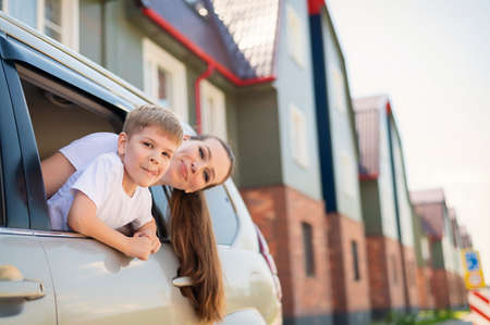 Traveling by car with the whole family. Happy Caucasian woman with son smiling sitting in the back seat of an SUV and looking out of a window. Car trip on summer vacation.