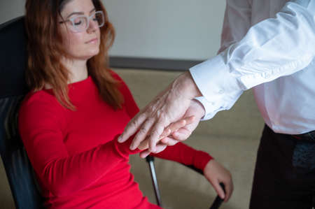 A red-haired woman sits in a chair with her hands closed and hands raised during gopnosis. Mature male hypnotherapist in session with a female patient. Alternative medicine for mental health. Cropped. Foto de archivo