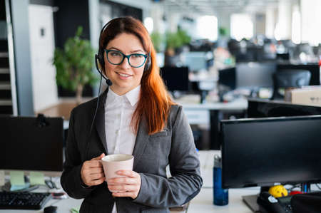 Happy office manager wearing glasses and headset holding mug. smiling female call center employee is politely answering customer calls. Hotline consultation. Woman working receptionist with pleasure.