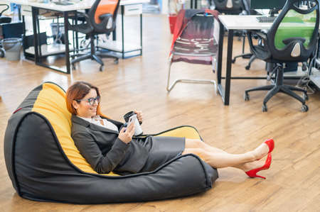 Business woman resting in a cozy bag chair and enjoys mobile. Female Manager at a break in a modern office. Caring for the convenience of employees. Beanbag in the workplace.