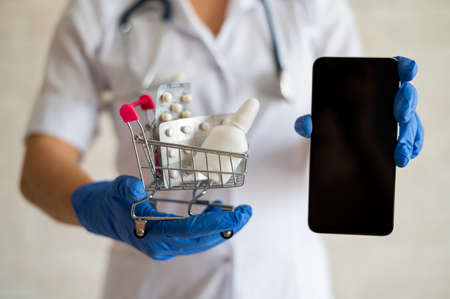 A faceless female doctor in a medical coat with a stethoscope holds a mini shopping trolley full of different medicines and a smartphone with a blank screen. Mobile application for the purchase of medicines. Online pharmacy Foto de archivo