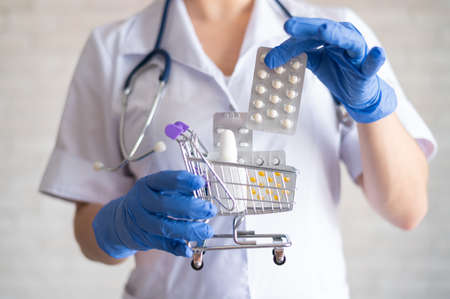 Faceless female doctor in rubber gloves puts a blister with tablets. A mini shopping trolley. The concept of buying medicine at the pharmacy. Drug store.