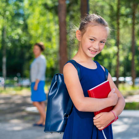Portrait of a diligent schoolgirl with a backpack and a book goes to first grade. Mom sends a happy daughter to elementary school.