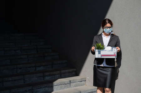 unemployed woman in a protective mask is standing with a box of personal belongings at the stairs. Business lady fired. The global economic crisis. Reduction of work due to the companys bankruptcy.